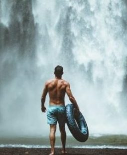 Man With Rubber Tyre Approaches Large Waterfalls.