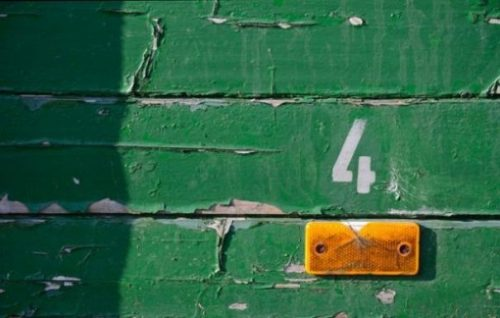Number Four Symbol On Faded Peeling Green Wood Wall With Orange Light Reflector Under The Symbol.