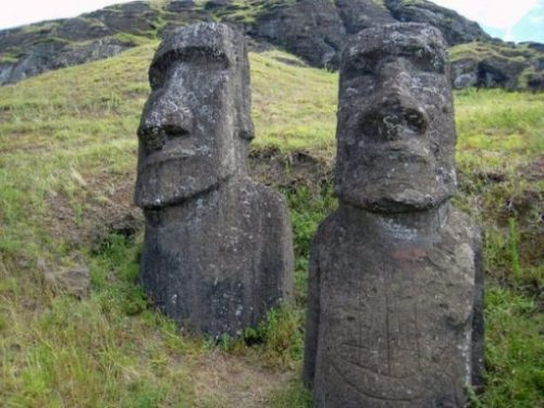 Featured Image Of A Pair Of The Easter Island Stone Statues In A Rocky Landscape.