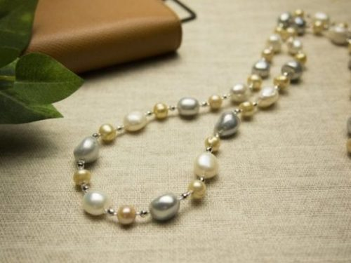 Polished Varietal Jewelled Pearl Necklace Lying On Cloth Surface With Plant And Journal In The Background.