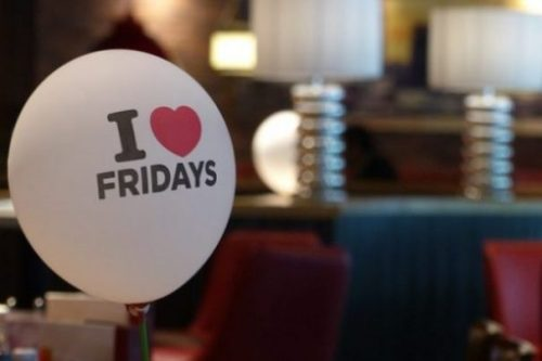 An I Love Fridays Balloon Displayed In A Low Lit Room.