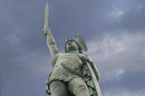 Stone Statue Of A Hero With Sword Held Upright.