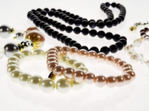Several Different Colored Pearl Necklaces Loosely Strewn Around In Display.