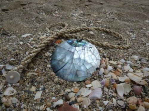 Mother Of Pearl Disc Necklace On A Rocky Beach.