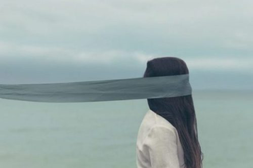 Standing On The Waters Edge A Long Black Haired Young Woman With A Long Blindfold On.