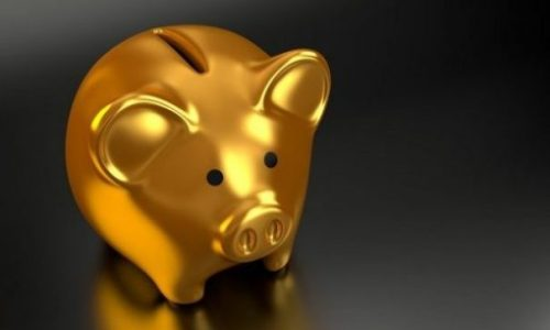 Close Up Image Of A Shiny Gold Piggybank With Dark Background.
