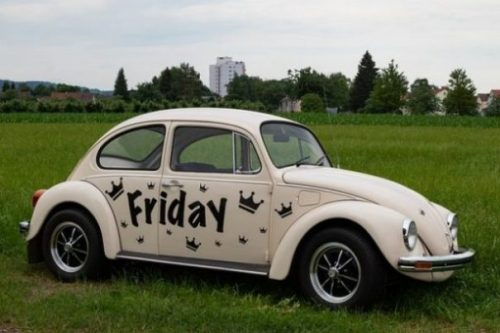 Featured Image Of A White Vw Car With Friday Painted On It's Side Sitting In A Grassy Field.
