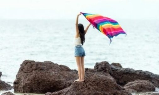 Image Of A Young Woman Holding Up A Bright Towel Near The Beach Shoreline.