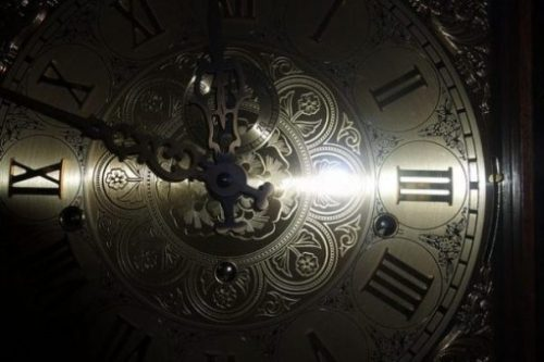 Close Up Image Of A Ornate Clock Face Partially Shadowed.