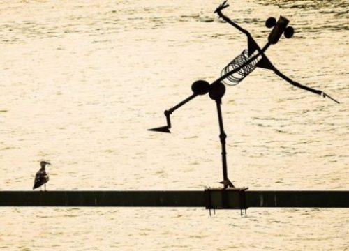Image Of A Bird Near And Looking At A Metal Man Statue Poised Precariously Above The Waters Surface.