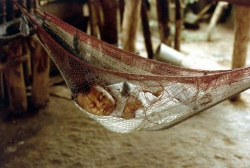 Image Of A Baby Asleep In A Net Hammock On Sandy Shores.