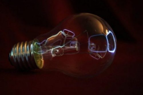 Close Up Image Of A Unconnected Light Bulb Reflecting Light On Its Glass.