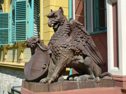 Image Of A Griffin Statue At A Building Entrance.