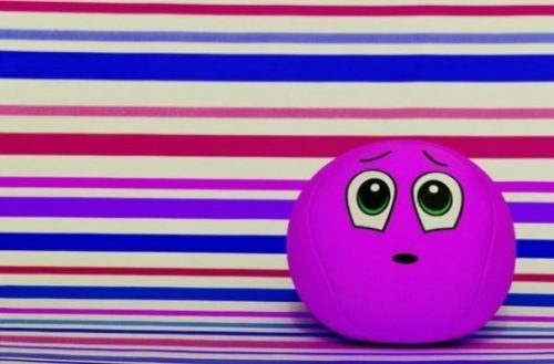 Featured Image Of A Purple Faced Ball Toy In Front Of A Striped Background.