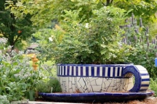 Image Of A Giant Size Blue And White Teacup Amidst A Herb Garden.