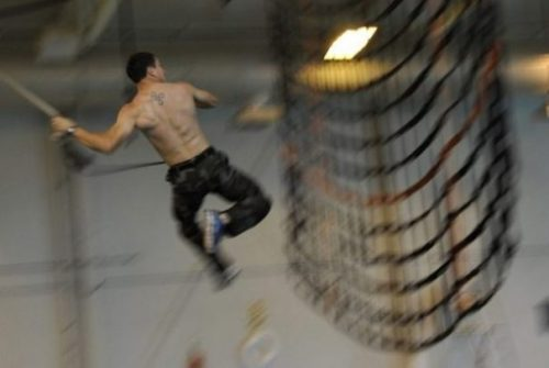 Image Of A Male Athlete Rope Swinging Towards A Net.