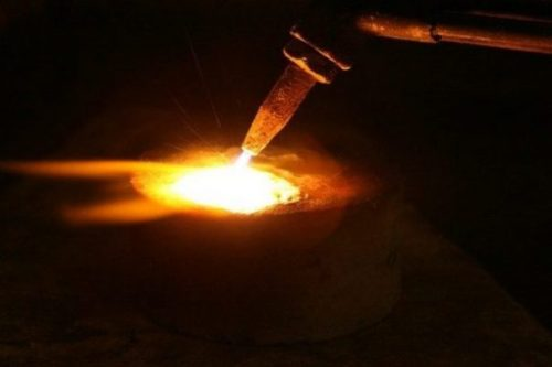 Image Closeup Of Acetylene Torch Alight Heating Metallic Components In A Pot.