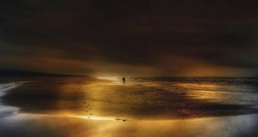 Image Of Beach Sunset With A Distant Figure And Footprints In The Sands.