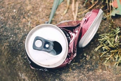 Image Closeup Of A Bent Twisted Aluminium Can On The Ground.