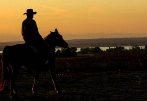 Image Of A Cowboy On A Horse Overlooking A Sunset Lit Town.