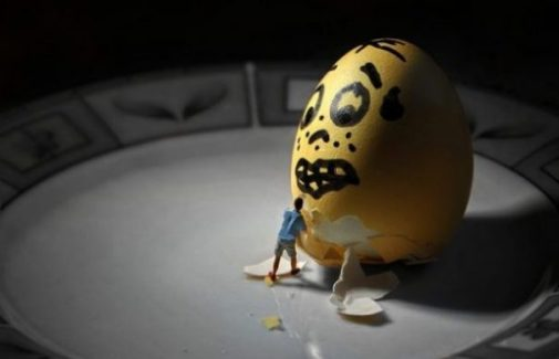 Image Of A Yellow Scared Faced Egg Watching A Tiny Toy Person Begin Deshelling.