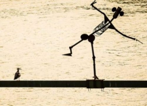 Featured Image Of A Metal Man Statue Leaning Over Water Whilst A Seagull Looks On.