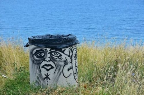 Featured Image Of A Face On A Bin Sitting Near The Sea Shore.