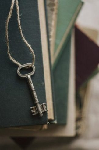 Image Of A Small Key Dangling Over Several Books.