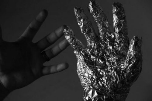 Image Of A Human Hand Next To An Aluminium Model.