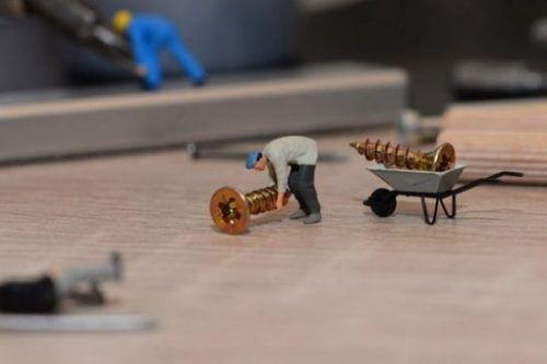 Image Of Tiny Toy Workers Barrowing Screws.