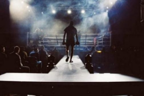 Image Of A Boxer Approaching The Lit Ring With A Crowd Shadowed In The Background.