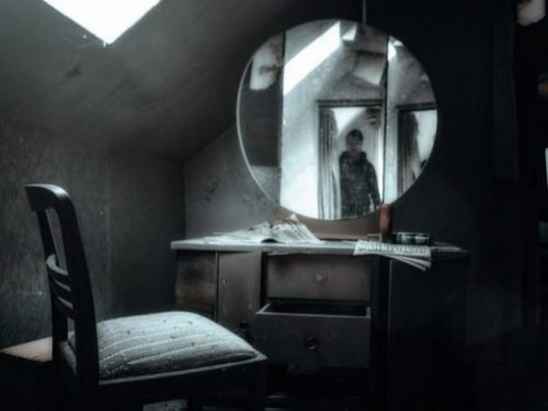 Image Of An Old Disused Room With Chair, Desk And Mirror Whilst In The Mirror A Reflected Figure Seen At The Doorway.