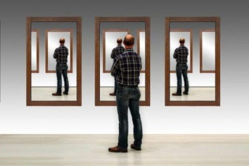 Featured Image Of A Elder Man Facing Reflections Of Self In 3 Mirrors.