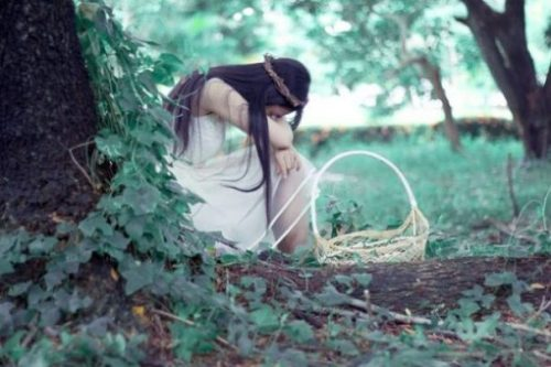 Image Of A Young Girl/Princess With Basket Alongside Sitting Alone In A Forest Setting.