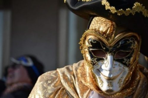 Image Of A Machiavellian Carnival Mask Wearer Eavesdropping On Others.