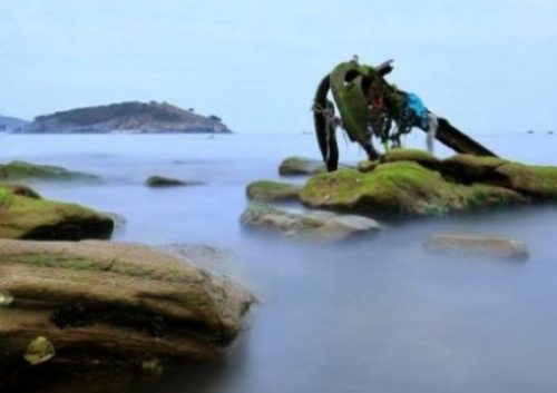 Image Of A Misty Shoreline Focusing On An Old Half Buried Anchor.