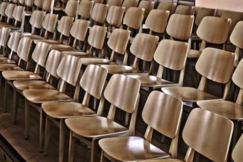 Featured Image Focusing On Several Rows Of Empty Chairs.