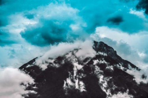 Image Of A Blueish Volcanic Mountain And Plume Colored On A Sky Blue Day.