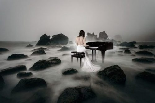 Featured Image Of A Misty Rocky Shore Where A Gowned Female Sits In Front Of A Piano.
