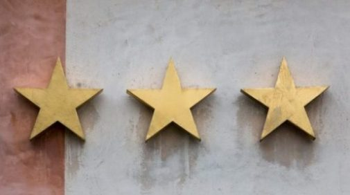 Image Of 3 Gold Five Pointed Stars On A Wall.