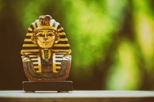 Image Of An Ancient Egyptian Mask Of A Pharaoh On A Ledge With Green Tree As Unfocused Background.