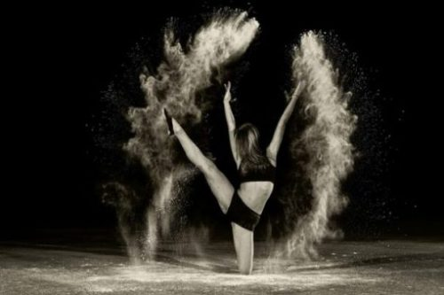 Image Of A Female Dancers And Her Moves Shown Via Arcs Of Powder.