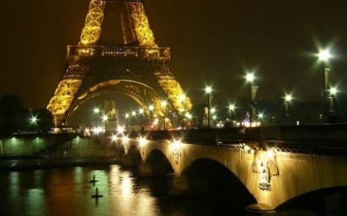 Image Of Paris At Night Highlighting Lower Section Of Eiffel Tower And Bridge.