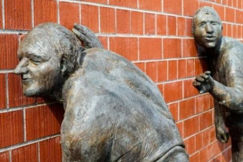 Image Of Two Statues Posed Listening Against A Brick Wall.